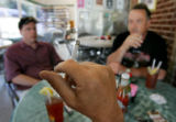 John Levy (cq), center, holds a cigarette while having lunch with Scott McPherson (cq), left, and...