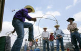 Jesse Jackson, left, shows off his roping skills to some friends by the chutes on the first day of...