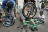 (left to right) Adonnis Rucker (cq), 10, Mackenzi Liman (cq), 23, and Adgn Noor,6, repair bicycles...