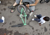 Adgn Noor,6, right, gets a helping hand with a bicycle repair Thursday afternoon in an alleyway...