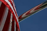 An American flag  is reflected in a railing on a boat, Tuesday morning, June 6, 2006, at Chatfield...