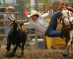 Clay Foulk, of Craig, leaps from his horse onto a steer while competing in steer wrestling at the...
