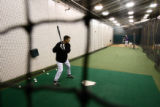 Jamey Carroll (cq) warms up in the practice batting cage in the Rockies clubhouse before the game...