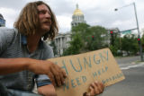 Leland Doane (cq), 41, a Denver-native, holds a sign asking for money on the corner of Broadway...
