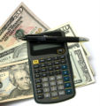 Checkbook, notepad and calculator used to make financial decissions