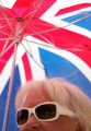 Karyn Hanson (cq), 56, of Arvada, wears sunglasses and stands under a British flag umbrella to...