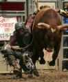 Jamon Turner, of Aurora, has his hand caught in the rigging in the bull-riding compewtition at the...