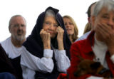 Eileen Maresh (cq, center), 84, of Denver covers her head as rain starts to fall as former...