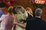 Center right with blonde hair, Elaine Meyer, mother to the deceased, gets a hug from an unknown...