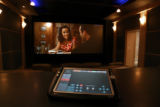 A Creston touch panel remote controls this home theater system which includes a 16ft screen at...