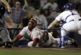 Angels baserunner Vladimir Guerrero injures himself in this head-first dive at home plate as he is...