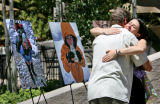 Craig Snowdon (cq) hugs Lindsay Warner (cq), left to right, in front of a photo display of Sue...