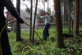 Patrick Brown, cq, center, an employee with Grand County Pest Control, sprays permetherin, a...