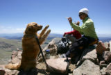 Ty Pixler (cq), right, feeds her dog Clifford, left, a treat at the summit of Mt. Bierstadt near...