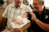 Benecio Martinez, cq, left, and Ernesto Romero, cq, right, admires their granddaughter Ashlyn...