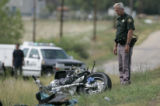 An officer with the Jefferson County Sheriffs Department  surveys the wreckage of a motorcycle...