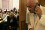 Lobbyist Nolbert Chavez (right) of Denver listens to a message on his cell phone while keeping...