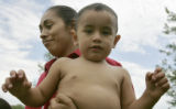 Silvia Soto smiles as she holds her baby , 2year old Giavanni, Wednesday afternoon June 21, 2006,...