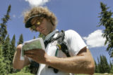 Aron Ralston(cq) reads a map in Koby Park near the Sloan Peaks Wilderness area during an 18 mile...
