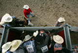 Bradley Dennison, of Cortez, is surrounded by fellow cowboys as he prepares for his first bareback...