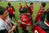 Ontario midfielder James Powless (#44, center) looks at his gold medal with teammates after...