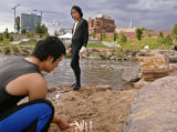 KAS036 Takahiro Haneda, left, lights candles in the sand in preparation for a dress rehearsal of a...