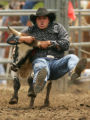 Jake Colletti, of Pueblo, jumps off his horse onto a steer in the steer wrestling competition at...