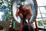 Paul Elliott (cq, center top), 4, peers out from inside a plexiglass bubble in a new playground...