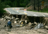 A photographer on a tour of one of dozens of washed out sections of road along HWY 67 is dwarfed...