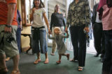 Claire Qualls, 2 1/2, holds hand with her mom, Melanie Mitchell (cq), right, and friend Stephanie...