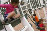 KAS047 Magda Rodriguez, 3, left, watches Danny Wilder, 3, right, play on a swing that's part of...