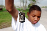 (Denver, Colo., April 22, 2004) Kolade Arije,16, holds up a medallion that he had made to remember...