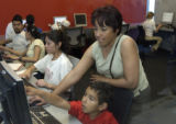 (LAKEWOOD, Colo., May 4, 2004) Maria Corran works with her son Antonio Rosales,5, on a computer in...