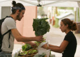 Tristen Waters (cq), of Boulder, left, buys organic produce from Kristen Asbury (cq), 14, from...