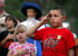 Forrest Farris (cq, right), 9, and his sister Kira (cq, left), 7, both of Conifer, honor the flag...