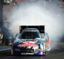 Whit Bazemore burns out his tires before his run at the 27th annual Mopar Mile-HIgh NHRA Nationals...