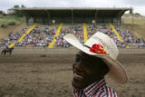 Bull-rider Jamon Turner, of Aurora, smiles while hanging out in the chutes at the Colorado State...