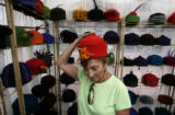 Susanne York(cq), of Castle Pines North, tries on an original hat creation by Nordland,...