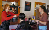 Nathalie Lien (cq), middle, gets her hair cut by stylist Talie Ayers (cq) , left, while Erynn...