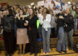 Danielle Montgomery, cq, (4th from left: white shirt) wife of Cpt. Kevin L. Montgomery reacts...