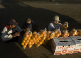 **1/31/06** Efren Hernandez, left, sells a bag of oranges to brothers Ruben and Juan Santos, both...