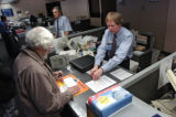 Post Office customer Les Roper (cq-left) takes care of some business with window clerk Steve Cowan...