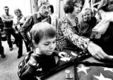 (FOREGROUND LT. TO. RT.) Jacob Gohl (CQ), 8, of Aurora helps family members Ronald Krings (CQ), of...