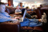 U.S. Army Captain Jeremy Jeffery, cq, Fort Irwin, works on his laptop in the USO center during a...