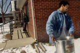 Carlos Martinez carries water from his home to his uncles' home at Quigg Newton homes in Denver...