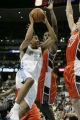 Andre Miller drives against Kareem Rush for a basket in the 1st period as the Denver Nuggets host...