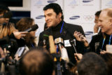 Italian skiing legend Alberto Tomba (center) speaks to a horde of reporters during the grand...