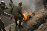 (NYT) KANDAHAR, Afghanistan -- Feb. 7, 2006 -- AFGHANISTAN-3 -- A police officer drags the body of...
