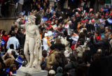 The Olympic Torch passes by a statue of Neptune in the Piazza Vittorio Emanuele II Wednesday...