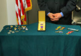 Colorado State Treasurer Mark Hillman displays a Purple Heart medal at a press conference Thursday...